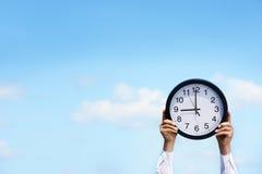 Επιχειρηματίας που κρατά ένα ρολόι ενάντια στο μπλε ουρανό Στοκ φωτογραφία με δικαίωμα ελεύθερης χρήσης