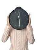 Επιχειρηματίας που κρατά ένα ρολόι μπροστά από το πρόσωπό της Στοκ Φωτογραφία
