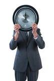 Επιχειρηματίας που κρατά ένα ρολόι μπροστά από το πρόσωπό του Στοκ Εικόνα