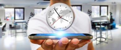 Επιχειρηματίας που κρατά ένα ρολόι πέρα από το κινητό τηλέφωνό του Στοκ φωτογραφίες με δικαίωμα ελεύθερης χρήσης