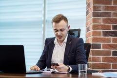Επιχειρηματίας που κρατά ένα τηλέφωνο κυττάρων και που γράφει sms το μήνυμα στο offi Στοκ Φωτογραφίες