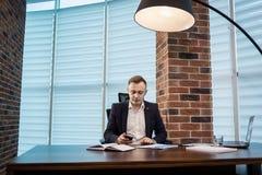 Επιχειρηματίας που κρατά ένα τηλέφωνο κυττάρων και που γράφει sms το μήνυμα στο offi Στοκ φωτογραφίες με δικαίωμα ελεύθερης χρήσης
