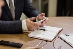 Επιχειρηματίας που κρατά ένα τηλέφωνο κυττάρων και που γράφει sms το μήνυμα στο offi Στοκ εικόνες με δικαίωμα ελεύθερης χρήσης