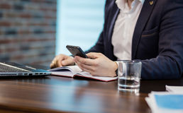 Επιχειρηματίας που κρατά ένα τηλέφωνο κυττάρων και που γράφει sms το μήνυμα στο offi Στοκ φωτογραφία με δικαίωμα ελεύθερης χρήσης