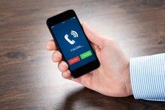 Επιχειρηματίας που κρατά ένα τηλέφωνο με την μπλε οθόνη και το τηλεφωνικό ringi Στοκ φωτογραφία με δικαίωμα ελεύθερης χρήσης