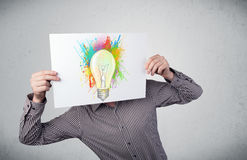 Επιχειρηματίας που κρατά ένα χαρτόνι με τους παφλασμούς χρωμάτων και lightbul Στοκ φωτογραφίες με δικαίωμα ελεύθερης χρήσης