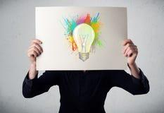 Επιχειρηματίας που κρατά ένα χαρτόνι με τους παφλασμούς χρωμάτων και lightbul Στοκ Φωτογραφία