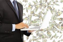 Επιχειρηματίας που κρατά ένα lap-top με τη βροχή χρημάτων Στοκ εικόνα με δικαίωμα ελεύθερης χρήσης