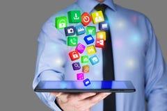Επιχειρηματίας που κρατά ένα PC ταμπλετών με τα κινητά εικονίδια εφαρμογών στην εικονική οθόνη τρισδιάστατη απεικόνιση Διαδίκτυο  Στοκ Φωτογραφία
