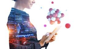 Επιχειρηματίας που κρατά ένα tabalet με μια δέσμη των σφαιρών που ανωτέρω Μικτά μέσα στοκ φωτογραφία