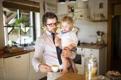 Επιχειρηματίας που κρατά λίγο γιο στα όπλα, που πίνει τον καφέ Στοκ Φωτογραφία
