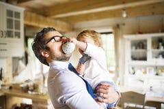 Επιχειρηματίας που κρατά λίγο γιο στα όπλα, που πίνει τον καφέ Στοκ φωτογραφία με δικαίωμα ελεύθερης χρήσης