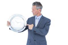 Επιχειρηματίας που κρατά και που παρουσιάζει ένα ρολόι Στοκ εικόνες με δικαίωμα ελεύθερης χρήσης