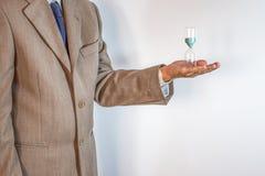 Επιχειρηματίας που κρατά μια κλεψύδρα απομονωμένη στο άσπρο υπόβαθρο Στοκ Εικόνες
