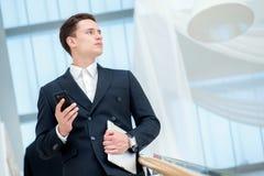 επιχειρηματίας που κρατά Νέος επιχειρηματίας που στέκεται το ο Στοκ Φωτογραφία