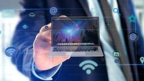 Επιχειρηματίας που κρατά να περιβάλει υπολογιστών από app και το κοινωνικό ico Στοκ Φωτογραφία
