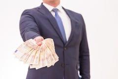 Επιχειρηματίας που κρατά πενήντα ευρο- τραπεζογραμμάτια στα χέρια του, που δίνουν σε κάποιο Στοκ φωτογραφία με δικαίωμα ελεύθερης χρήσης