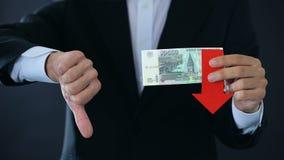 Επιχειρηματίας που κρατά τα ρωσικά τραπεζογραμμάτια ρουβλιών που παρουσιάζουν αντίχειρες πάνω-κάτω, πτώση απόθεμα βίντεο