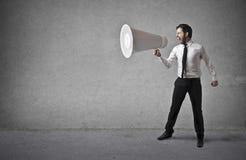 Επιχειρηματίας που κρατά τεράστιο megaphone Στοκ εικόνες με δικαίωμα ελεύθερης χρήσης