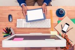Επιχειρηματίας που κρατά την ψηφιακή ταμπλέτα καθμένος στο γραφείο υπολογιστών Στοκ φωτογραφία με δικαίωμα ελεύθερης χρήσης