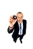 Επιχειρηματίας που κρατά τη μαύρη σφαίρα μπιλιάρδου Στοκ Εικόνες