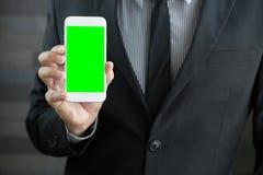 Επιχειρηματίας που κρατά το κινητό έξυπνο τηλέφωνο με την πράσινη οθόνη Στοκ Εικόνα