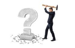 Επιχειρηματίας που κρατά το μεγάλο σφυρί για να συντρίψει το ερωτηματικό φιαγμένο από πέτρα Στοκ Φωτογραφία