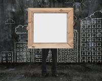 Επιχειρηματίας που κρατά το ξύλινο κενό πλαισίων whiteboard με τα κτήρια Στοκ Εικόνες