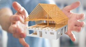 Επιχειρηματίας που κρατά το τρισδιάστατο σπίτι σχεδίων απόδοσης ατελές στο εκτάριό του Στοκ Εικόνες