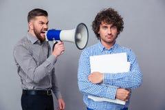 Επιχειρηματίας που κραυγάζει μέσω megaphone σε ένα άλλο άτομο Στοκ εικόνα με δικαίωμα ελεύθερης χρήσης