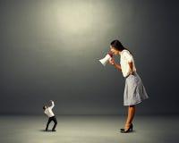 Επιχειρηματίας που κραυγάζει στο μικρό τρομαγμένο άτομο Στοκ Φωτογραφίες