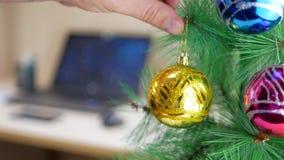 Επιχειρηματίας που κρεμά τη χρυσή σφαίρα Χριστουγέννων σε ένα χριστουγεννιάτικο δέντρο απόθεμα βίντεο