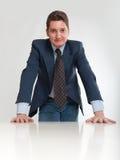 Επιχειρηματίας που κλίνει σε ένα άσπρο γραφείο Στοκ Φωτογραφίες