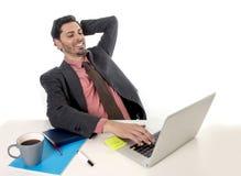 Επιχειρηματίας που κλίνει στην καρέκλα που λειτουργεί στο lap-top υπολογιστών γραφείων που φαίνεται ευτυχής ικανοποιημένος και χα Στοκ Εικόνες