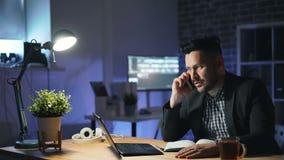 0 επιχειρηματίας που μιλά κινητό τηλεφωνικό στο σκοτεινό γραφείο τη νύχτα απόθεμα βίντεο