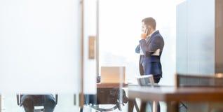 Επιχειρηματίας που μιλά σε ένα κινητό τηλέφωνο κοιτάζοντας μέσω του παραθύρου Στοκ εικόνα με δικαίωμα ελεύθερης χρήσης
