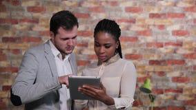 Επιχειρηματίας που μιλά στην αμερικανική επιχειρηματία afro που κοιτάζει στον υπολογιστή ταμπλετών απόθεμα βίντεο