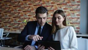Επιχειρηματίας που μιλά στις επιχειρηματίες που κοιτάζουν στον υπολογιστή ταμπλετών απόθεμα βίντεο