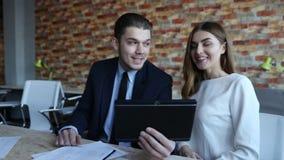 Επιχειρηματίας που μιλά στις επιχειρηματίες που κοιτάζουν στον υπολογιστή ταμπλετών φιλμ μικρού μήκους