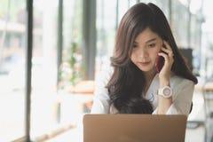 Επιχειρηματίας που μιλά στο κινητό τηλέφωνο στο γραφείο το νέο θηλυκό En Στοκ Φωτογραφία