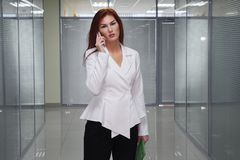 Επιχειρηματίας που μιλά στο κινητό τηλέφωνο στο διάδρομο του γραφείου στοκ εικόνες με δικαίωμα ελεύθερης χρήσης