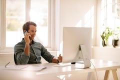 Επιχειρηματίας που μιλά στο κινητό τηλέφωνο εργαζόμενος στον υπολογιστή α Στοκ Εικόνες