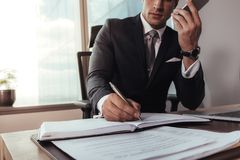 Επιχειρηματίας που μιλά στο κινητό τηλέφωνο και που κάνει τις σημειώσεις Στοκ Εικόνες