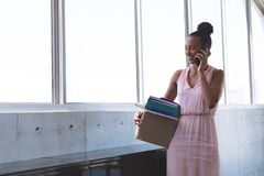 Επιχειρηματίας που μιλά στο κινητό τηλέφωνο κρατώντας τις ουσίες στο γραφείο στοκ εικόνες