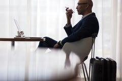 Επιχειρηματίας που μιλά στο κινητό τηλέφωνο στο σαλόνι αερολιμένων Στοκ Φωτογραφίες