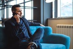 Επιχειρηματίας που μιλά στο κινητό τηλέφωνο στο σαλόνι γραφείων Στοκ εικόνα με δικαίωμα ελεύθερης χρήσης