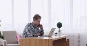 Επιχειρηματίας που μιλά στο κινητό τηλέφωνο χρησιμοποιώντας το lap-top στο γραφείο γραφείων απόθεμα βίντεο