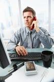 Επιχειρηματίας που μιλά στο τηλέφωνο γραμμών εδάφους στην αρχή Στοκ εικόνα με δικαίωμα ελεύθερης χρήσης