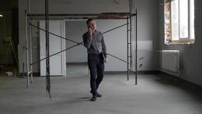 Επιχειρηματίας που μιλά στο τηλέφωνο στο εργοτάξιο οικοδομής απόθεμα βίντεο