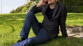Επιχειρηματίας που μιλά στο τηλέφωνο στο πάρκο, καθμένος στο χορτοτάπητα, που χαλαρώνει μετά από την εργάσιμη ημέρα απόθεμα βίντεο